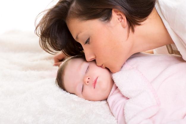 Dziewczynka i matka całuje jej kłamać szczęśliwego na bielu