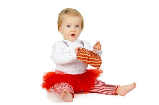 Dziewczynka i prezent odizolowywający na bielu