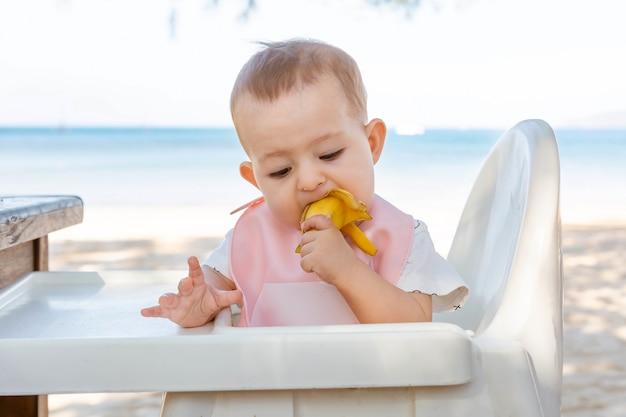 Dziewczynka je owsiankę tata karmi małą córeczkę łyżką na tropikalnej plaży