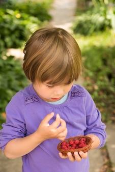Dziewczynka jedzenie malin z kosza w zielonym ogrodzie