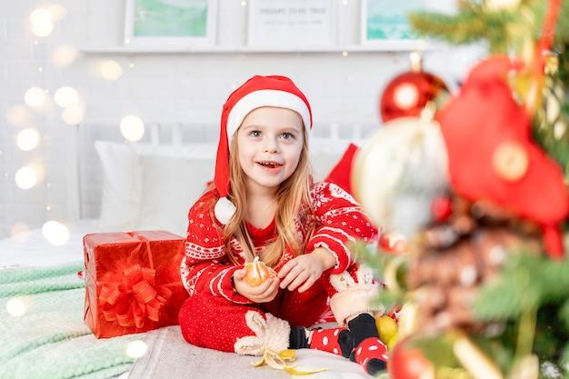 Dziewczynka jest na łóżku w domu jedząc mandarynki i czekając na nowy rok lub boże narodzenie w czerwonym kapeluszu świętego mikołaja i uśmiechając się ze szczęścia
