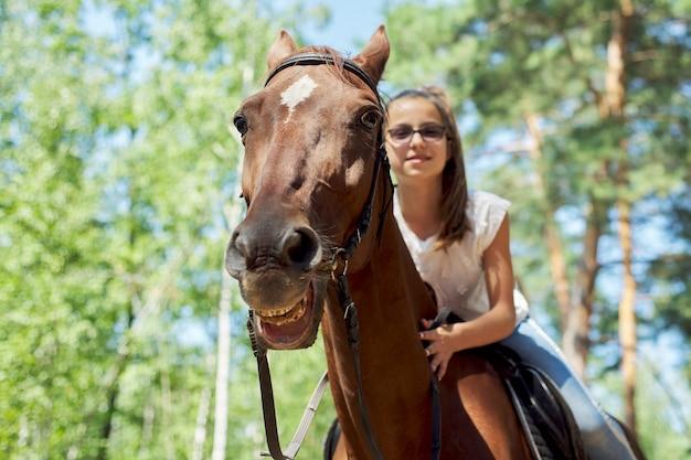 Dziewczynka jeździ konno, letnia przejażdżka konna w lesie, dziewczyna czule przytuliła konia.