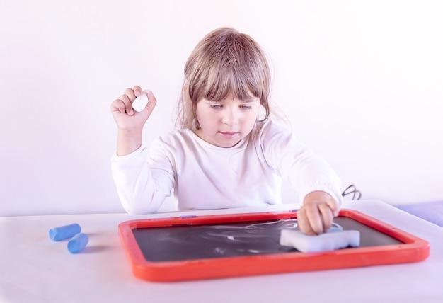 Dziewczynka kasuje rysunek na tablicy w domu