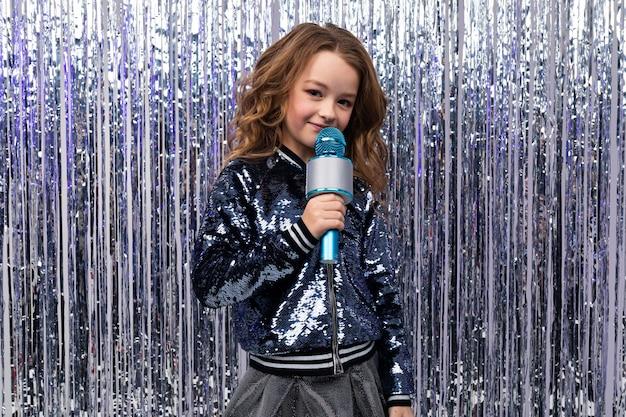 Dziewczynka kaukaski z mikrofonem na ścianie blichtru