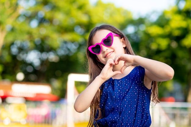 Dziewczynka latem w parku rozrywki pokazuje serce z rąk i uśmiecha się ze szczęścia w pobliżu karuzeli w okularach przeciwsłonecznych, koncepcja wakacji letnich i wakacji szkolnych