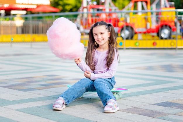Dziewczynka latem w wesołym miasteczku je watę cukrową na deskorolce i uśmiecha się ze szczęścia w pobliżu karuzeli, koncepcja wakacji i wakacji szkolnych