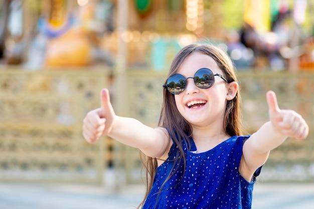 Dziewczynka latem w wesołym miasteczku pokazuje klasie górny palec i uśmiecha się ze szczęścia przy karuzeli w okularach przeciwsłonecznych, koncepcja wakacji letnich i wakacji szkolnych