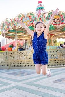 Dziewczynka latem w wesołym miasteczku skacze ze szczęścia wokół karuzeli i śmiechu, koncepcji wakacji letnich i wakacji szkolnych