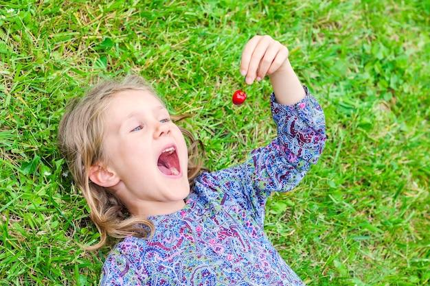 Dziewczynka leżąc na trawie z wiśnią w dłoni