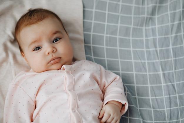 Dziewczynka leżąca na plecach na łóżku w jasnej sypialni, ubrana w jasną sukienkę. spokojne dziecko kochanie 3 miesiące. kopia przestrzeń