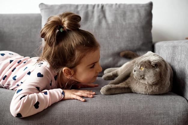 Dziewczynka leży na kanapie i bawi się z kotem