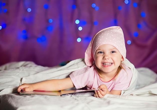 Dziewczynka leży w łóżku w szlafmycy z książką dla dzieci i uśmiecha się