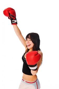 Dziewczynka ma na sobie rękawice bokserskie z podniesioną ręką
