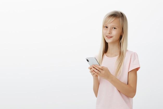 Dziewczynka może lepiej korzystać z gadżetów niż rodzice. portret pewnie urocze małe dziecko z ładnymi oczami w różowej koszulce, trzymając smartfon i uśmiechając się
