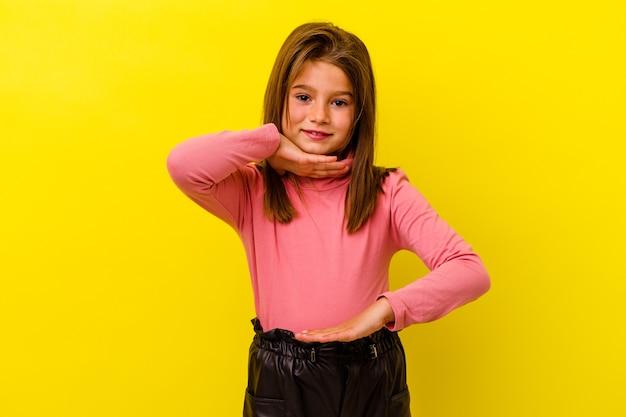 Dziewczynka na białym tle na żółtej ścianie, trzymając coś obiema rękami