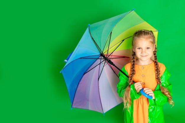 Dziewczynka na odosobnionym zielonym tle z parasolką i płaszczem przeciwdeszczowym uśmiecha się, miejsce na tekst