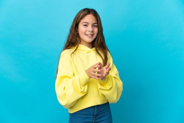 Dziewczynka na pojedyncze niebieskie tło brawo po prezentacji na konferencji
