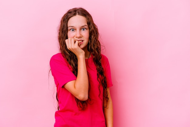 Dziewczynka na różowej ścianie obgryzająca paznokcie, nerwowa i bardzo niespokojna
