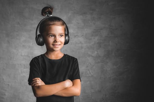 Dziewczynka nosi słuchawki stojąc na białym tle na szarej ścianie, słuchając muzyki
