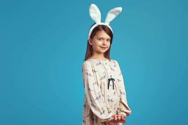 Dziewczynka nosi uszy królika i uśmiecha się na niebieskiej ścianie