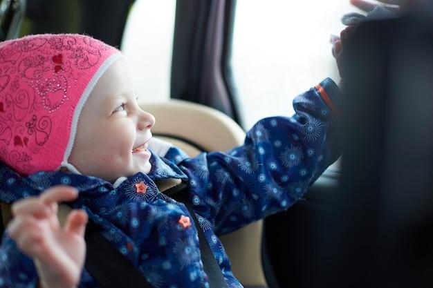 Dziewczynka o niebieskich oczach siedząca na foteliku dla dziecka na tylnym siedzeniu samochodu przy oknie