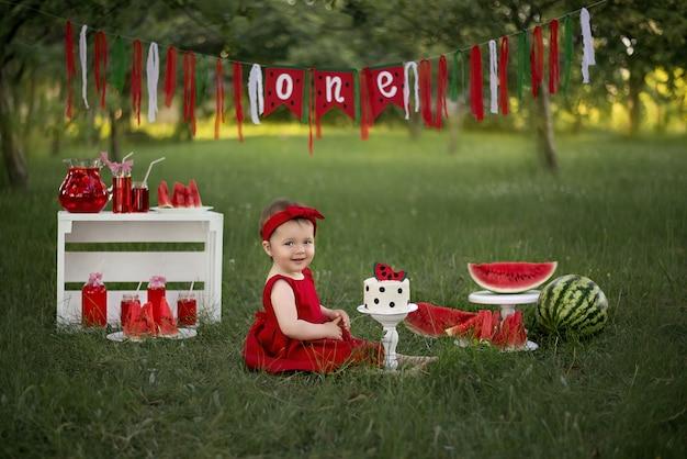 Dziewczynka obchodzi urodziny. przed dziewczyną jest ciasto i dużo arbuzów.