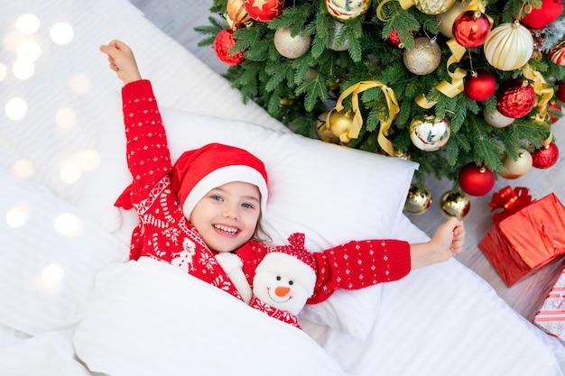 Dziewczynka obudziła się pod choinką w czerwonym swetrze i czapce świętego mikołaja w sylwestra lub boże narodzenie w białym łóżku z bałwanem w ramionach
