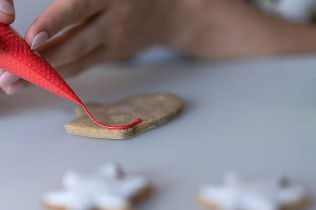 Dziewczynka ozdabia świąteczne ciasteczka białym cukrem pudrem