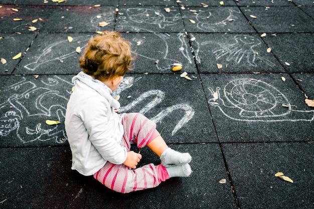 Dziewczynka patrzy na rysunki kredą na podłodze placu zabaw.