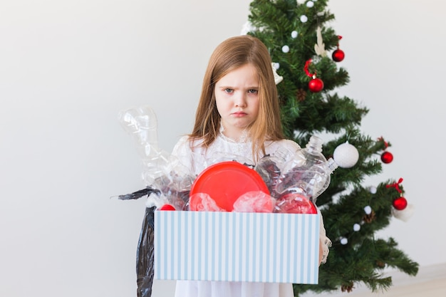 Dziewczynka patrzy z otwartymi oczami i zmartwioną miną, trzymając pudełko z różnymi plastikowymi odpadami nad ścianą choinki.
