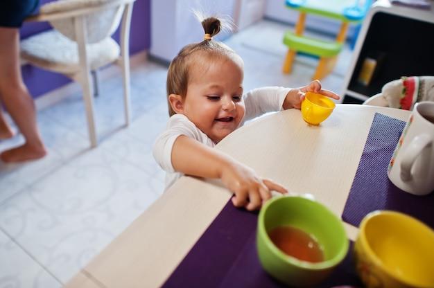 Dziewczynka pić sok kompotowy w kuchni, szczęśliwe chwile dzieci.