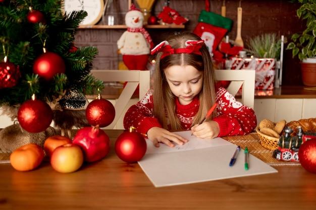 Dziewczynka pisze list do świętego mikołaja w ciemnej kuchni pod choinką z czerwonymi kulkami, koncepcja nowego roku i bożego narodzenia