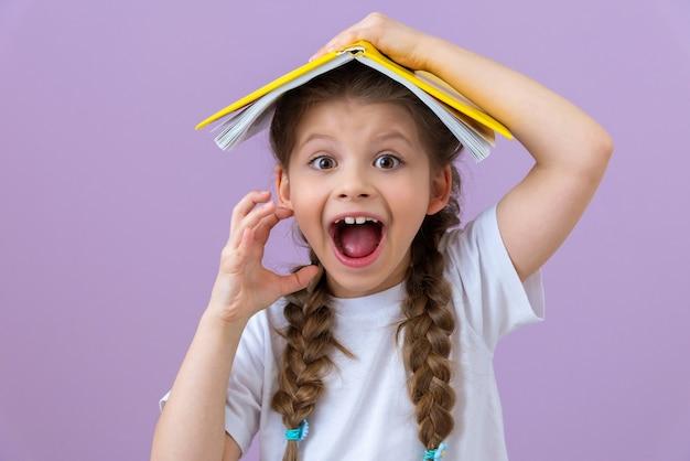Dziewczynka położyła otwartą książkę na głowie i otworzyła usta.