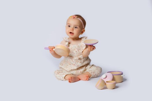 Dziewczynka portret bawi się potrawami drewniane zabawki na białym tle