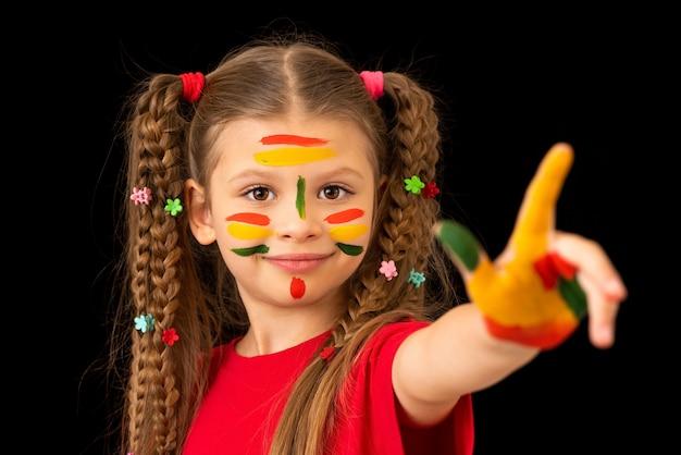 Dziewczynka posmarowała farbą ręce i twarz.
