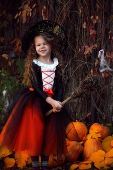 Dziewczynka przebrana za małą czarownicę w pomarańczowej bufiastej spódniczce i spiczastym czarnym kapeluszu z miotłą przy dyniach halloweenowych w jesiennym parku po południu