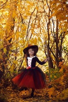 Dziewczynka przebrana za małą czarownicę w pomarańczowej spódniczce i spiczastym czarnym kapeluszu z miotłą w jesiennym halloweenowym parku z dynią