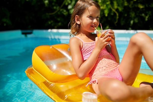 Dziewczynka relaksując się w basenie, ciesząc się opalenizny, pije sok na nadmuchiwanym żółtym materacu w wodzie na rodzinne wakacje