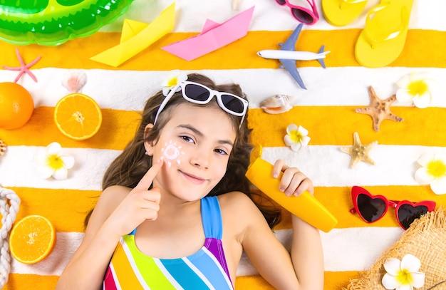Dziewczynka rozmazuje na skórze krem przeciwsłoneczny. selektywna ostrość. dziecko.