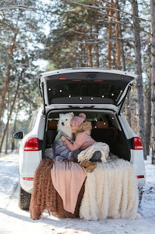 Dziewczynka siedząca w bagażniku samochodu ze swoim zwierzakiem, białym psem samoyed