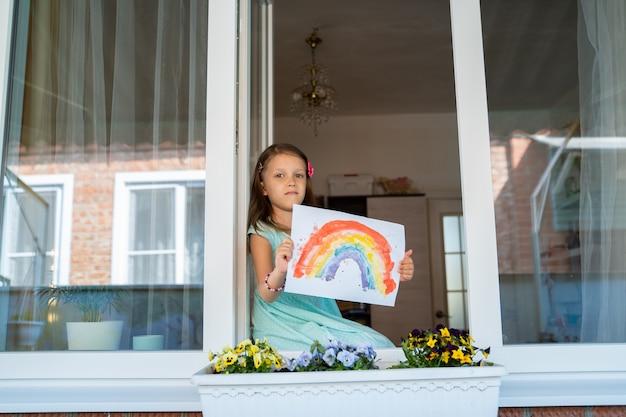 Dziewczynka siedzi i wygląda przez okno z tęczowym wzorem w dłoniach, izolując dom przed pandemią koronawirusa