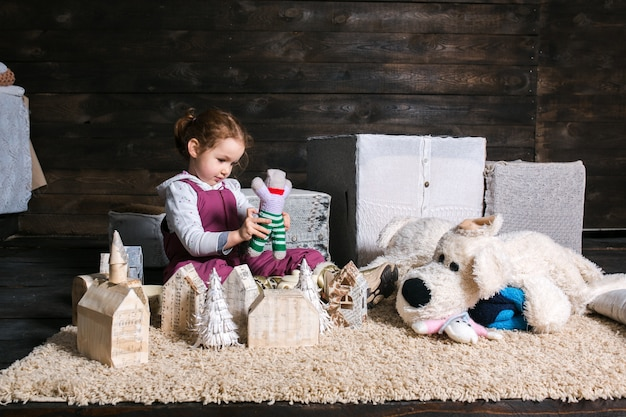 Dziewczynka siedzi na dywan bawi się z marionetką