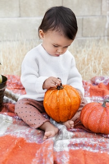 Dziewczynka siedzi na miękkim kocu i trzymając pomarańczowy dyni na zewnątrz