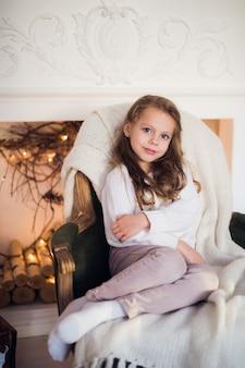 Dziewczynka siedzi na wygodnym fotelu zawinięta w koc