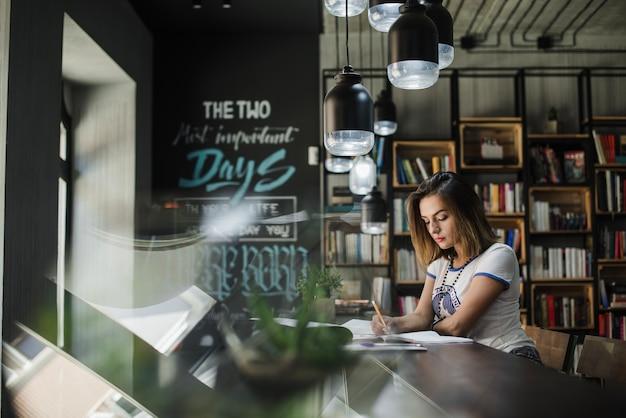 Dziewczynka siedzi przy stole pisania
