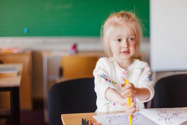 Dziewczynka siedzi przy stole w klasie