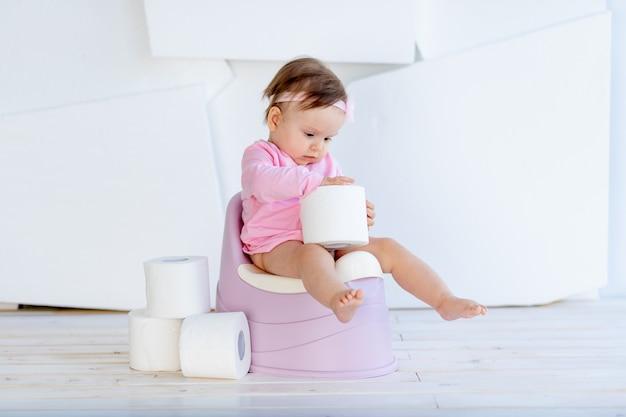 Dziewczynka siedzi w białym pokoju na nocniku w różowe ubrania z papierem toaletowym