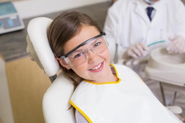Dziewczynka siedzi w fotelu dentyści noszenie okularów ochronnych
