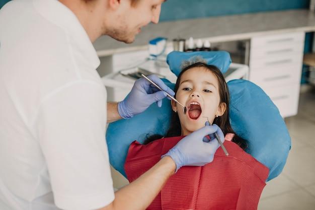 Dziewczynka siedzi w fotelu stomatologicznym z otwartymi ustami, podczas gdy jej dentysta dziecięcy robi badanie zębów.