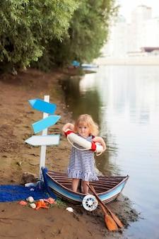 Dziewczynka siedzi w łodzi, przebrana za marynarza, na piaszczystej plaży z muszelkami nad morzem